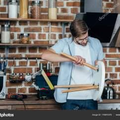 Kitchen Stools Lowes Cabinet Doors 集中的年轻人在镜片修理厨房凳子 图库照片 C Igorvetushko 178970370