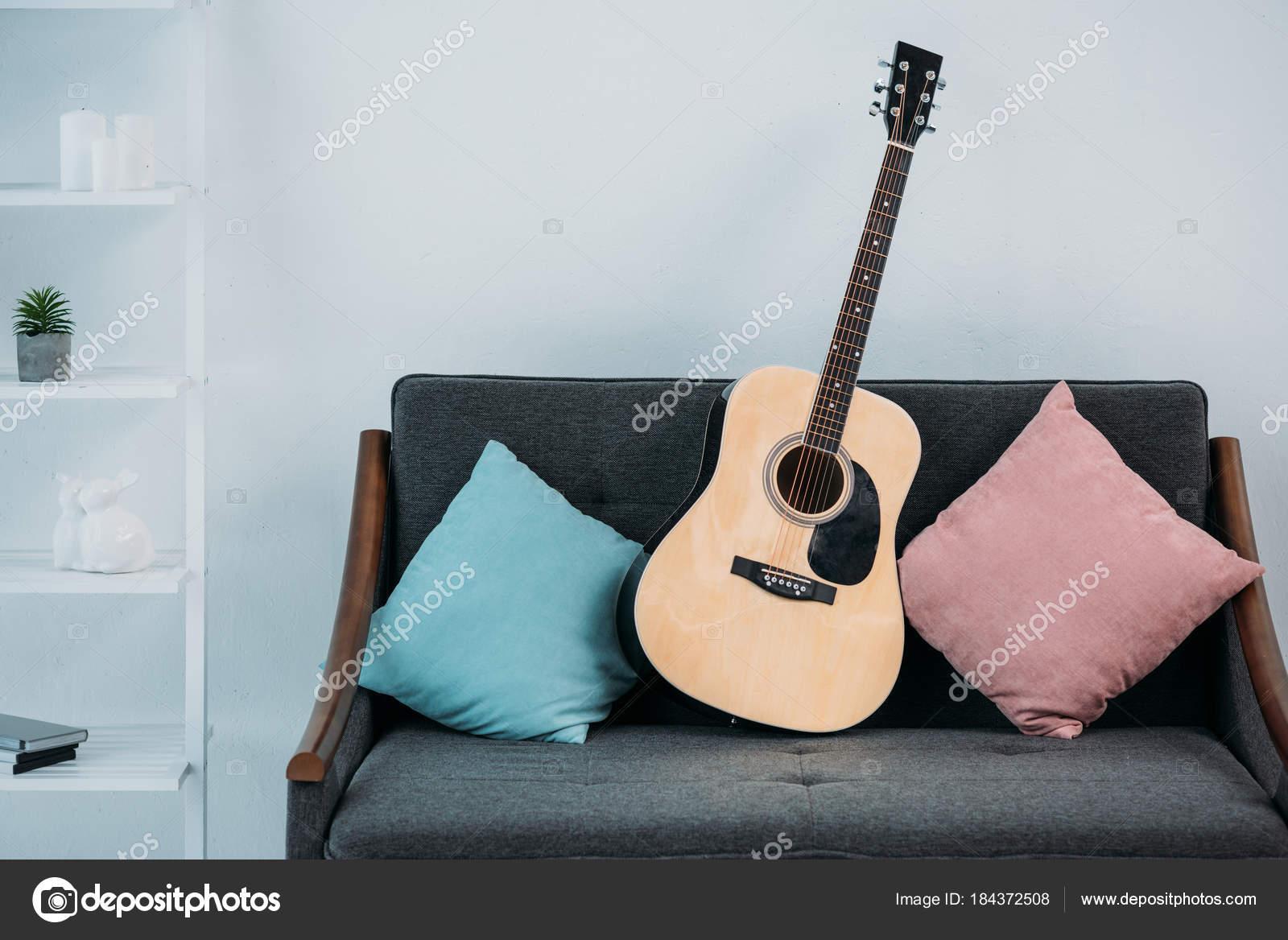 nahaufnahme der akustikgitarre auf sofa mit kissen wohnzimmer stockfoto
