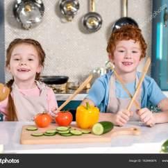 Kids Wooden Kitchen Unfinished Oak Cabinets Home Depot 可爱的孩子手持木制器皿在厨房里一起做饭时微笑 图库照片 C Allaserebrina