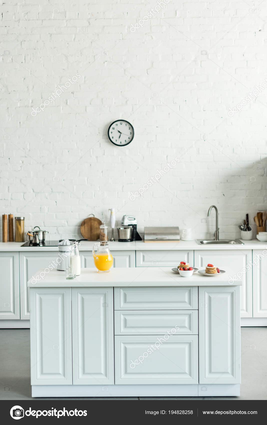 kitchen counter wall storage 现代光厨房的内部与薄饼和橙汁在厨房柜台 图库照片 c vitalikradko 194828258