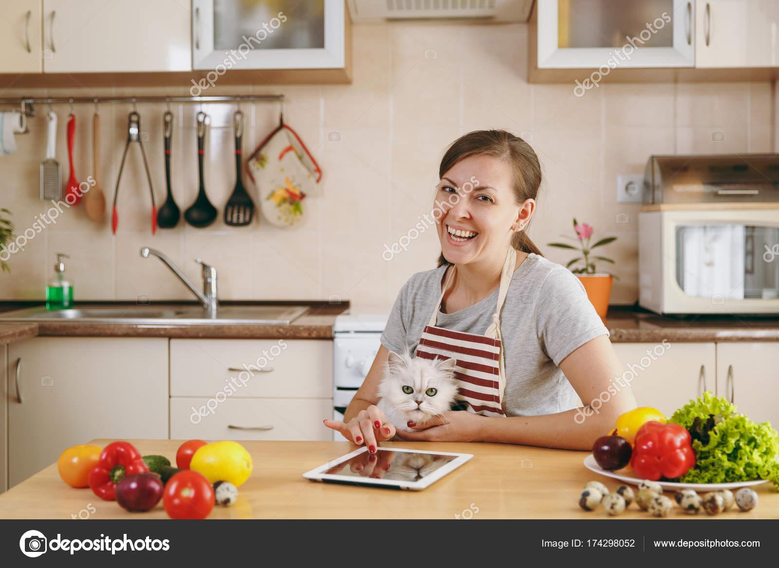nice kitchen tables four hole faucets 一个年轻漂亮的女人与白色的波斯猫在厨房与片剂在桌子上 蔬菜沙拉 节食 那个年轻漂亮的女人带着白色的波斯猫在厨房里 桌子上放着平板电脑 节食概念 健康的生活方式 在家做饭