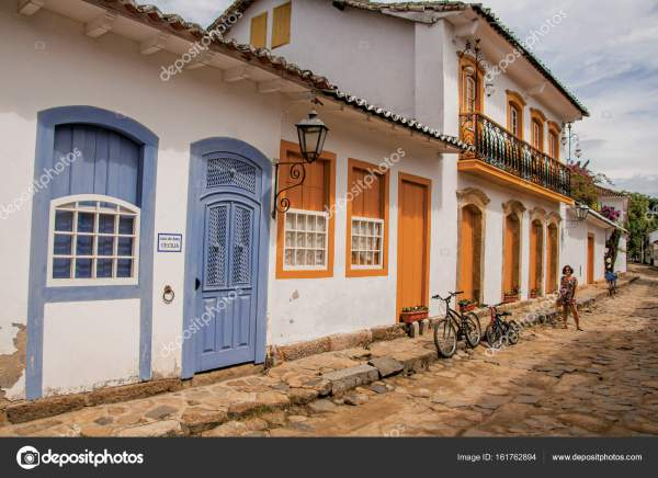 Cobblestone Alley With Colorful Houses And Woman In