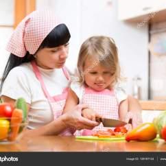 Macys Kitchen Aid Particle Board Cabinets 母亲教孩子在厨房里做沙拉 妈妈和孩子用刀在砧板上切菜 幸福的家庭 为 妈妈在厨房里做沙拉的教学孩子 母亲和孩子用刀在砧板上切菜 为晚餐准备食物的烹饪概念 照片作者oksun70