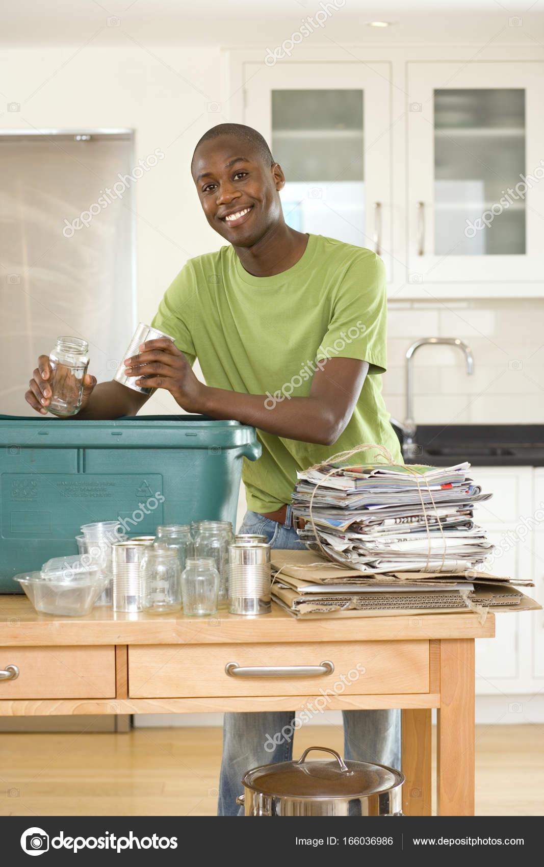 kitchen recycle bin how to fix up old cabinets 年轻人把空玻璃罐子和罐头入回收站在厨房里 图库照片 图库