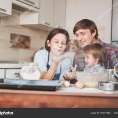 Kid Kitchens Pictures Of Kitchen Islands 年轻的父母和可爱的小孩在厨房里玩地板 图库照片 C Dmytrobandakbo 177277492