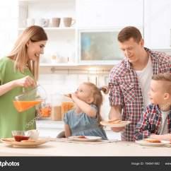 Kid Kitchens Kitchen Hutch Cabinet 父母和可爱的小孩在厨房餐桌上吃着可口的烤面包 图库照片
