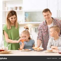 Kid Kitchens Cast Iron Kitchen Stove 父母和可爱的小孩在厨房餐桌上吃着可口的烤面包 图库照片