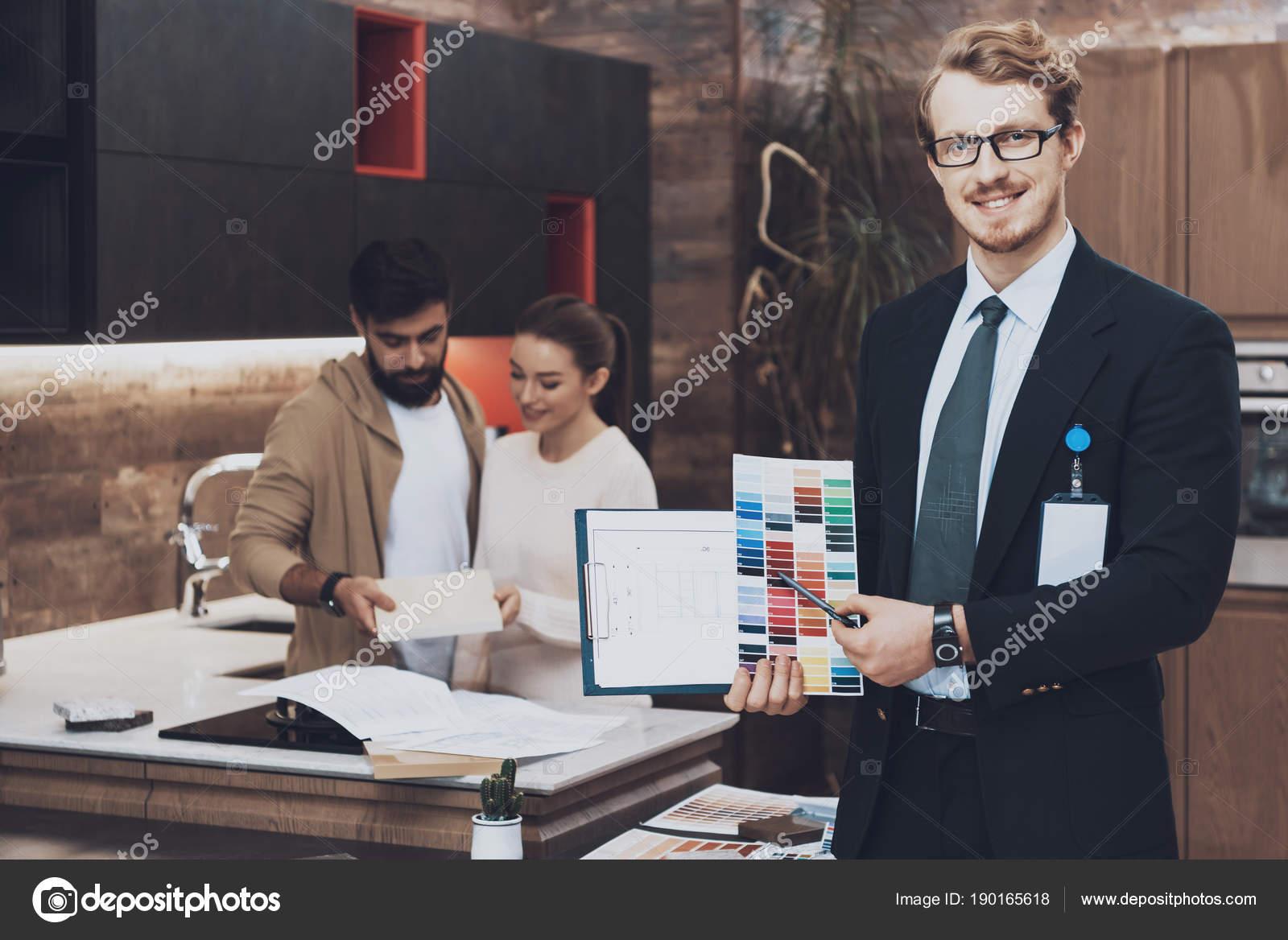 kitchens store smart tv kitchen 经理在服装展示五颜六色的色板和蓝图与情侣客户在厨房商店背景 图库照片 经理在服装展示五颜六色的色板和蓝图与情侣客户在厨房商店