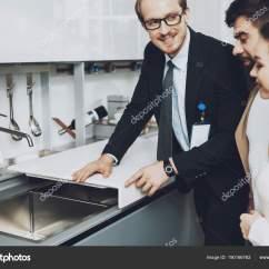 Kitchens Store Glass Kitchen Tables And Chairs 经理在西装陈列厨房水槽与盖子对夫妇顾客在厨房商店 图库照片 图库