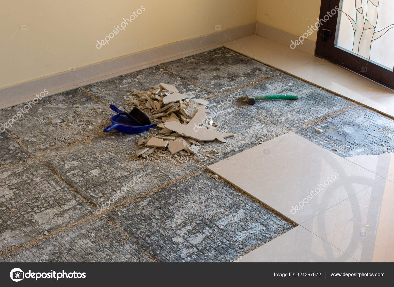 home renovation of ceramic tiles in an entrance way breaking up the tiles diy and cleaning up broken pieces before laying new tiles with mortar and cement stock photo image by c