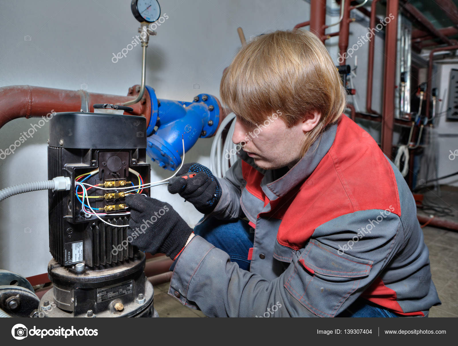 hight resolution of repair pump heating system mechanic connects wires to electric motor stock photo