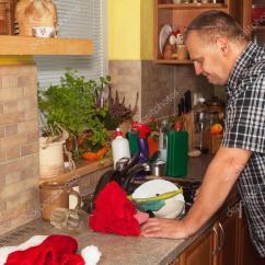Kitchen Aid Bowls Round Table With Leaf 在厨房里的家庭作业 男人洗脏盘子在厨房的水槽 国内在晚会结束后清理