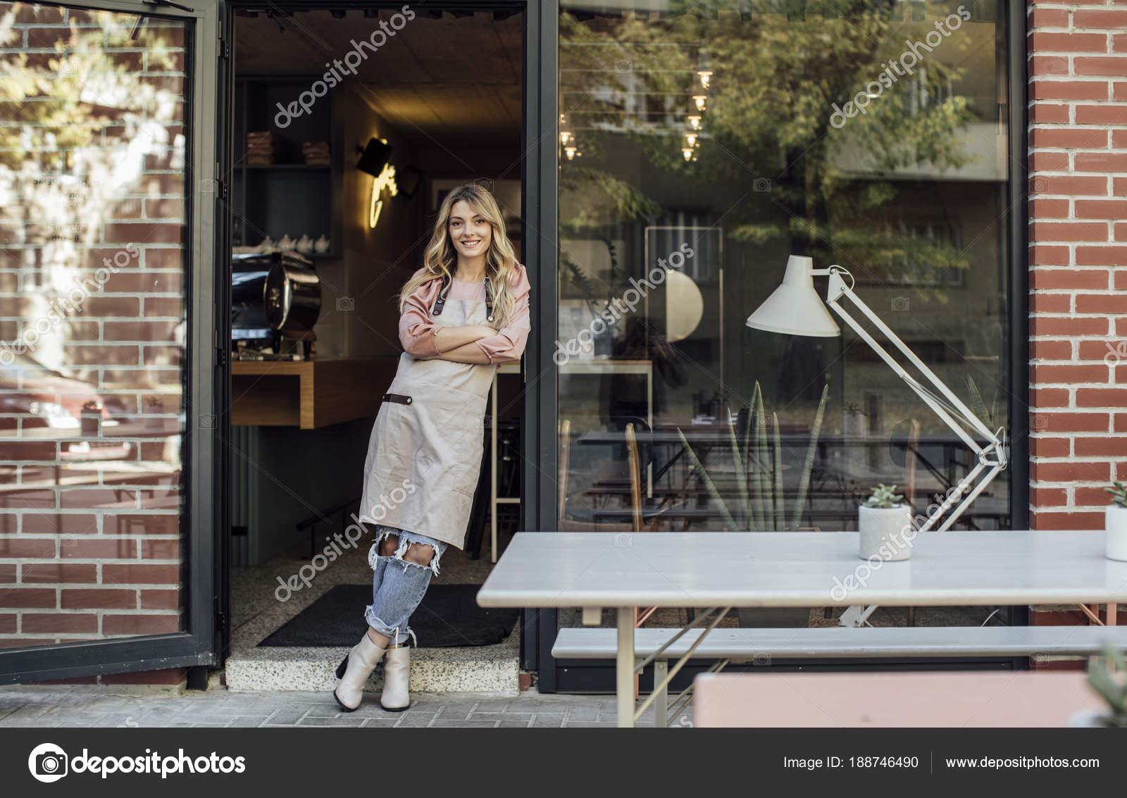 portrait de la belle blonde caucasienne femme serveuse tablier et debout devant son cafe restaurant image de luminastock