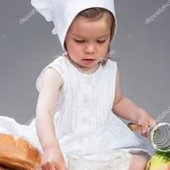 Kitchen Whisk Cabinet Trim Installation 白种人女孩在与厨房玻璃器皿用拂尘在工作室工作的厨师制服 图库照片 白种人女孩在与厨房玻璃器皿用拂尘在工作室工作的