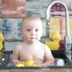 Kitchen Kid Lights For Under Cabinets 可爱的微笑婴儿洗澡在厨房水槽孩子玩泡沫和肥皂气泡在阳光明媚的厨房与 可爱的微笑婴儿洗澡在厨房水槽孩子玩泡沫和肥皂气泡在阳光