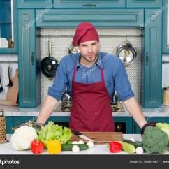 Kitchen Prep Table Memphis Cabinets 英俊的白种人年轻人在围裙站立在桌与菜 在家烹调在厨房准备膳食与木表面 充满花哨的厨房用具 照片作者stetsik