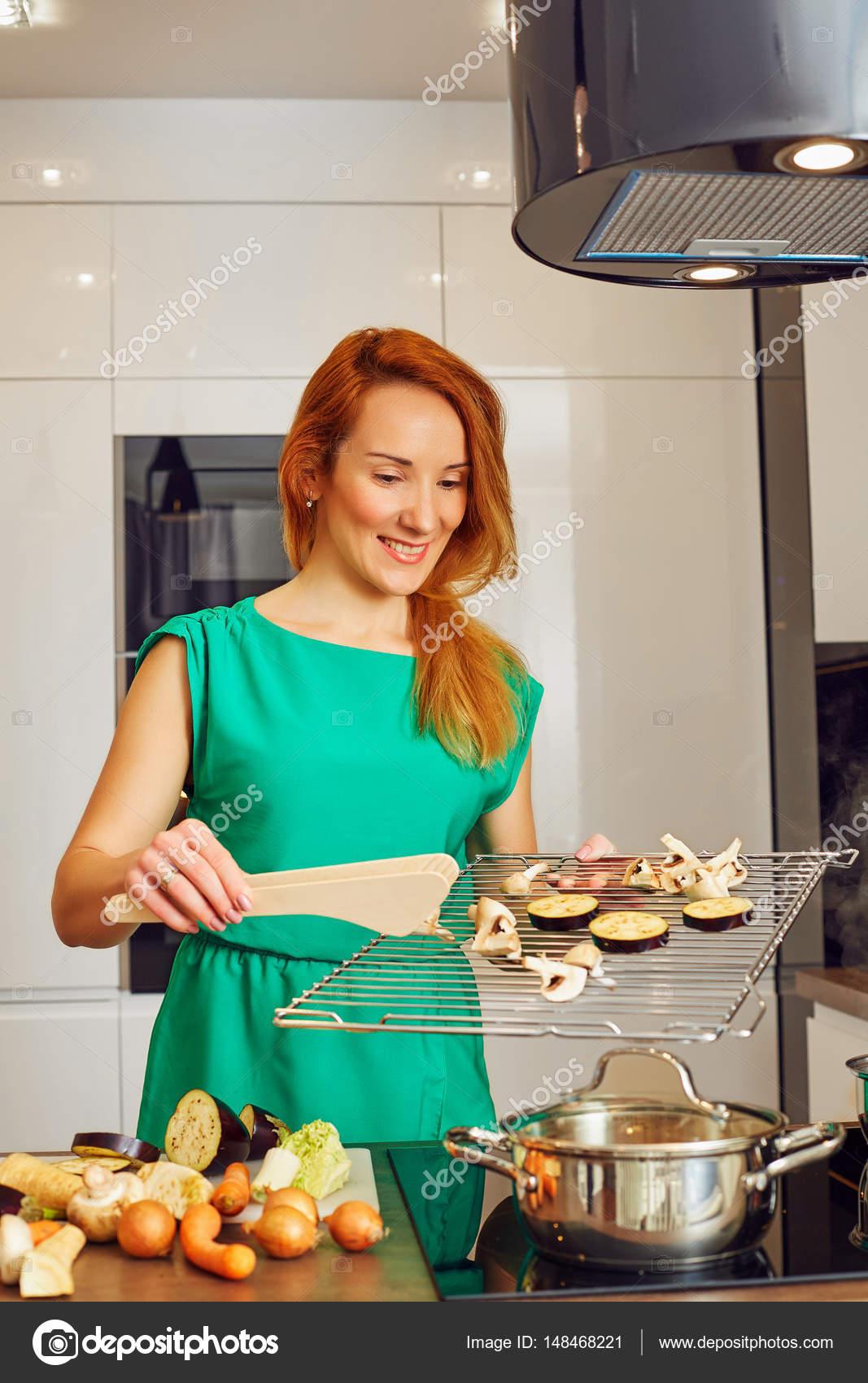 nice kitchen tables cherry island 漂亮微笑女人红头发站在厨房的桌子旁边和持有格栅与蔬菜 在高科技现代 漂亮微笑女人红头发站在厨房的桌子旁边和持有格栅