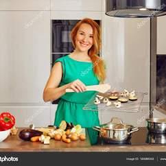 Nice Kitchen Tables Pan Set 漂亮微笑的女人红头发站在厨房的桌子旁边和持有格栅与蔬菜 看着相机在高 漂亮微笑的女人红头发站在厨房的桌子旁边和持有格