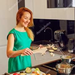 Nice Kitchen Tables Gray Table And Chairs 漂亮微笑女人红头发站在厨房的桌子旁边和持有格栅与蔬菜 在高科技现代 漂亮微笑女人红头发站在厨房的桌子旁边和持有格栅