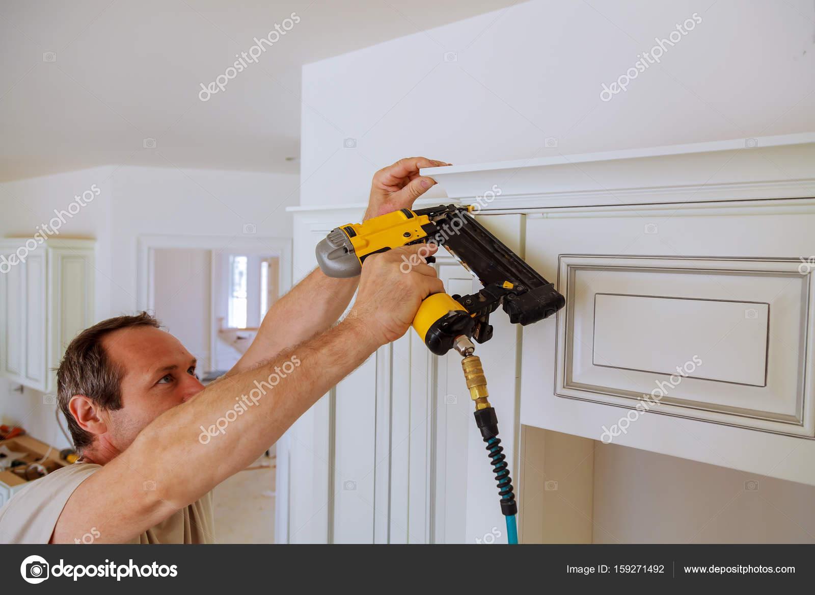 upper kitchen cabinets curio cabinet 木匠使用射钉枪在皇冠造型上厨柜框架修剪的布拉德 图库照片 c photovs 木匠使用射钉枪在皇冠造型上厨柜框架修剪的布拉