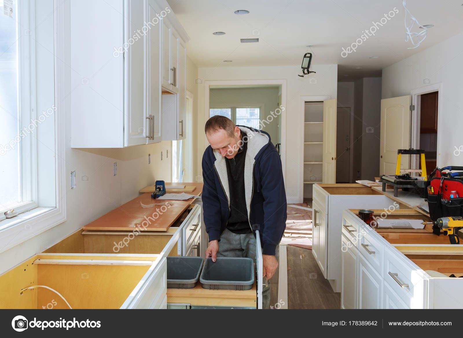 kitchen cabinets set cart table 工人设置在白色的柜子上用螺丝刀安装厨柜 图库照片 c photovs 178389642