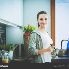 Kitchen Prep Station Inexpensive Flooring Options For 年轻女人准备站在桌子旁边的时候厨房里的薄煎饼 在厨房里的女人 在厨房 在