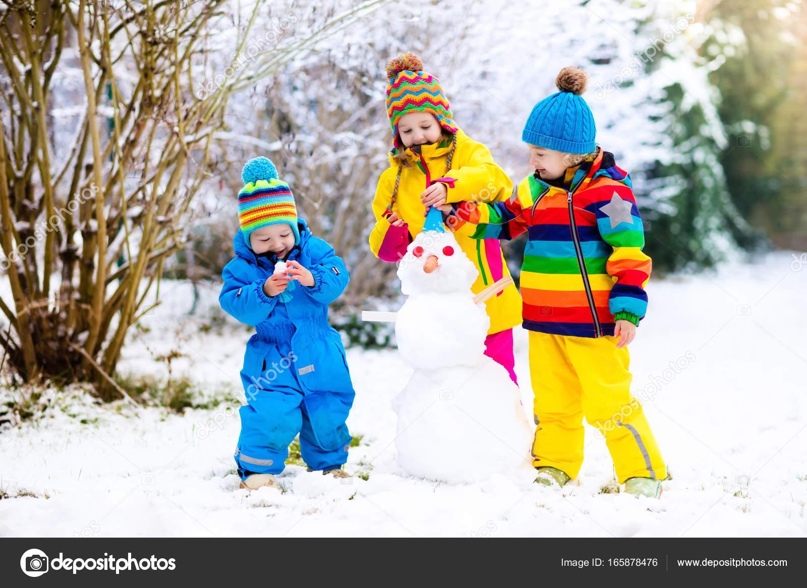 Kids Building Snowman Children In Snow Winter Fun