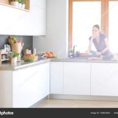 Nice Kitchen Tables Luxury Appliances 年轻漂亮的女人 坐在厨房的桌子在荷花的立场 图库照片 C Lenetssergey 图库