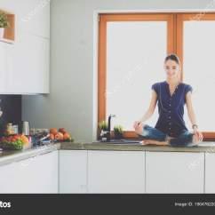 Nice Kitchen Tables Kmart 年轻漂亮的女人 坐在厨房的桌子在荷花的立场 图库照片 C Lenetssergey 图库