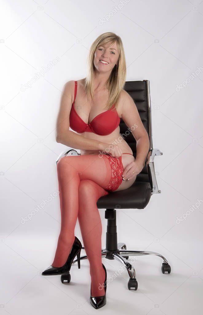 Secretaria sexy en ropa interior roja en una silla de