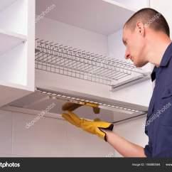 Kitchen Cabinets Set 32 Inch Undermount Sink 工人在厨柜里设置晾盘子的架子 图库照片 C Mkuchina 195880584