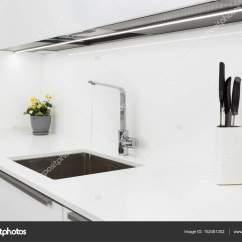 Blanco Kitchen Sink Cabinets Outlet 现代设计师铬在不锈钢厨房水槽水龙头 内部的明亮的白色厨房 图库照片