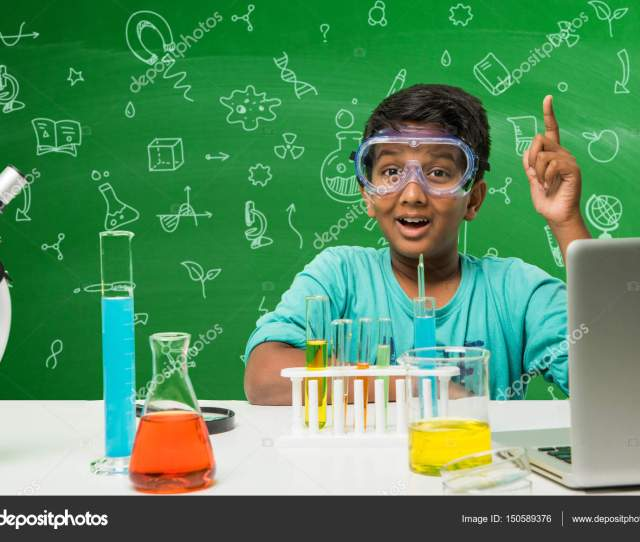 Kids And Science Concept Cute Indian Little Boy Busy Doing Science Or Chemistry Experiment With Test Tube And Flask With Safety Eye Glass Over Green