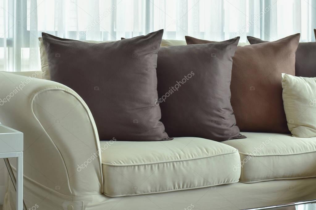 Cuscini marroni scuri impostazione sul divano di colore beige  Foto Stock  WorldWide_Stock
