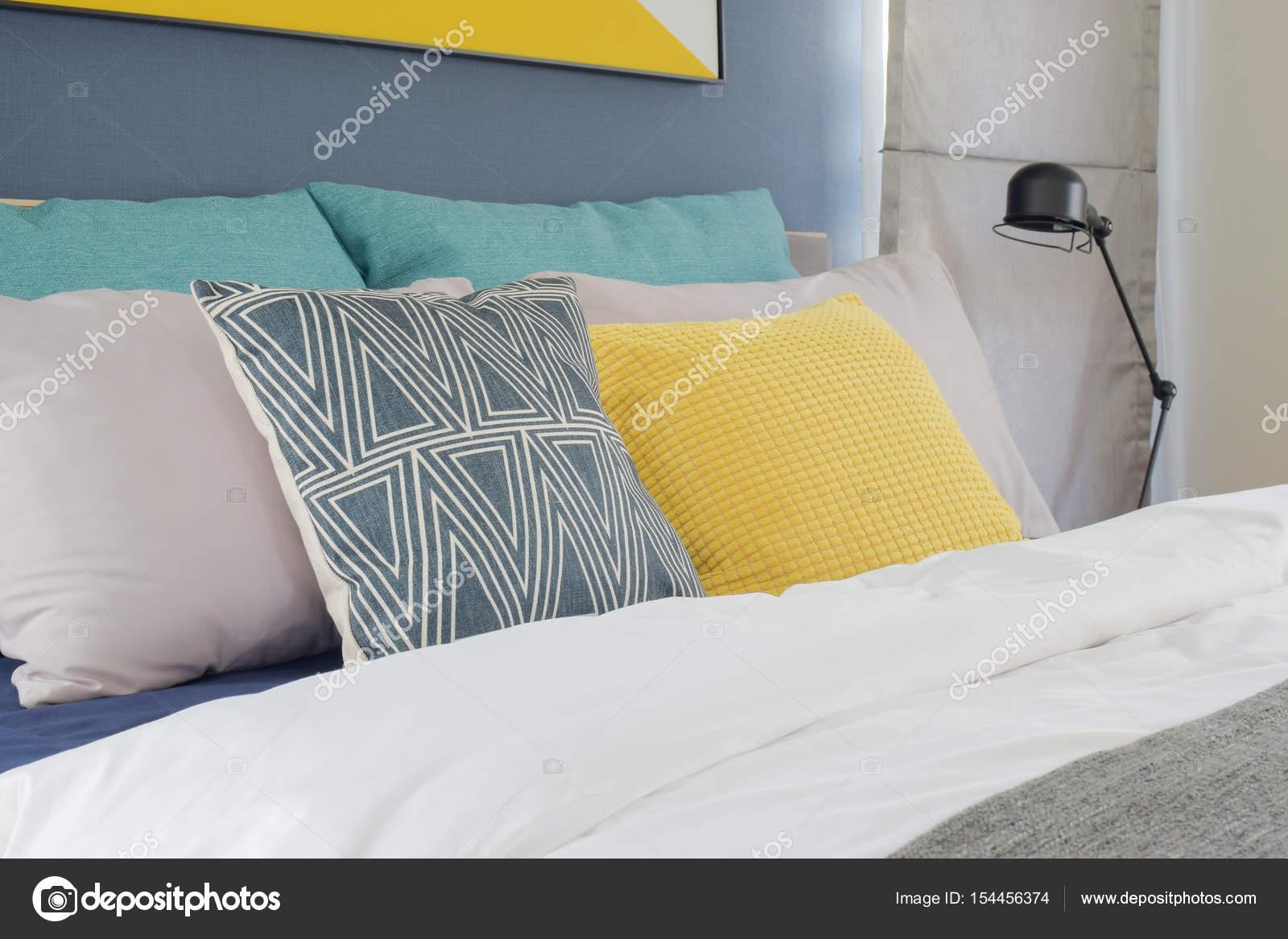 Geel grijs en turquoise kleur kussens instellen op bed in