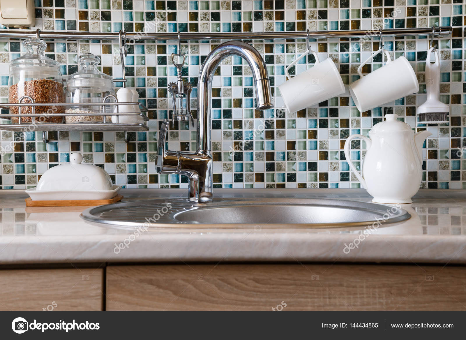 built in kitchen table garbage cans 厨房内饰和厨房用具 厨房的桌子 各种白色盘子和内置的厨房的水槽与金属 各种白色盘子和内置的厨房的水槽与金属漆水龙头 照片作者vladeephoto gmail com