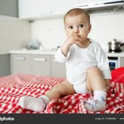 Nice Kitchen Tables Vintage Posters For 用红桌布坐在厨房桌子上的漂亮小男孩的画像当母亲拍儿子的照片时 图库 用红桌布坐在厨房桌子上的漂亮小男孩的画像当母亲