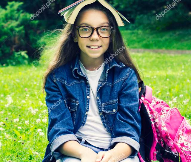 Beautiful Blonde Schoolgirl Girl In Jeans Shirt Reading A Book On Grass With A Backpack In The Park On A Sunny Summer Day Photo By Vallerato
