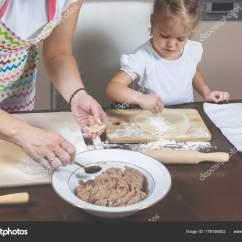 Macys Kitchen Aid Delta Single Handle Faucet Installation 小女孩和妈妈在家里的厨房里做饺子 图库照片 C Ovbelov 179195002