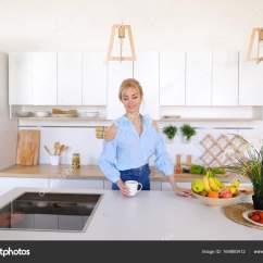 Nice Kitchen Tables Refinish Cabinets Cost 漂亮的女孩走进了厨房和伸展运动 享受早晨c 图库照片 C Sisterspro 有魅力的女人走过来和去厨房的桌子 举起双手向两侧上下能缓解紧张和花费手香早上新鲜咖啡 用轻松的笑容 站在中间的笑
