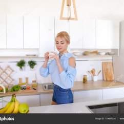Nice Kitchen Tables Island Light Fixtures 漂亮的女孩走进了厨房和伸展运动 享受早晨c 图库照片 C Sisterspro 有魅力的女人走过来和去厨房的桌子 举起双手向两侧上下能缓解紧张和花费手香早上新鲜咖啡 用轻松的笑容 站在中间的笑