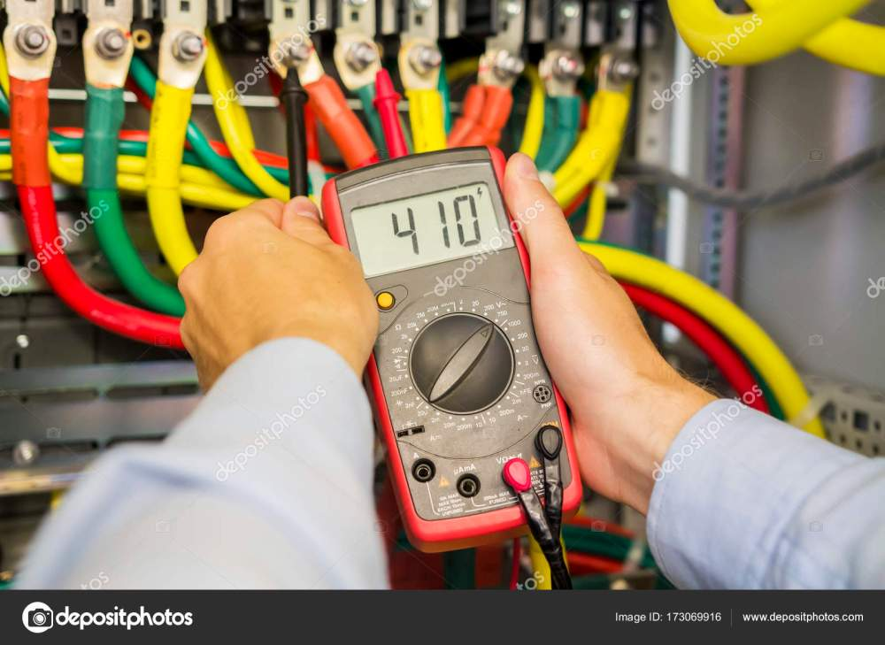 medium resolution of multimeter in hands of electrician in power high voltage three phase circuit box close up