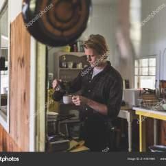 Traveling Kitchen Wine Cabinet 男人把咖啡倒在厨房的老木屋里英俊的金发男子身穿衬衫准备早餐和烹饪生活 男人把咖啡倒在厨房的老木屋里 英俊的金发男子身穿衬衫 准备早餐和烹饪 生活方式和旅行概念 照片作者william87
