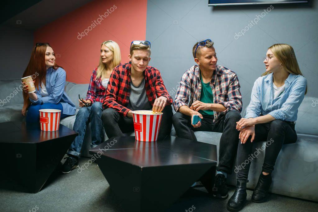 一群朋友吃爆米花 在電影院里等演出時間 坐在電影院的男男女女青年坐在坐在一個坐的拍座 — 圖庫照片© ...