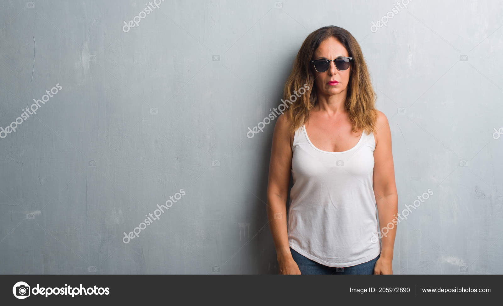 Middle Age Hispanic Woman Grey Wall Wearing Sunglasses Serious
