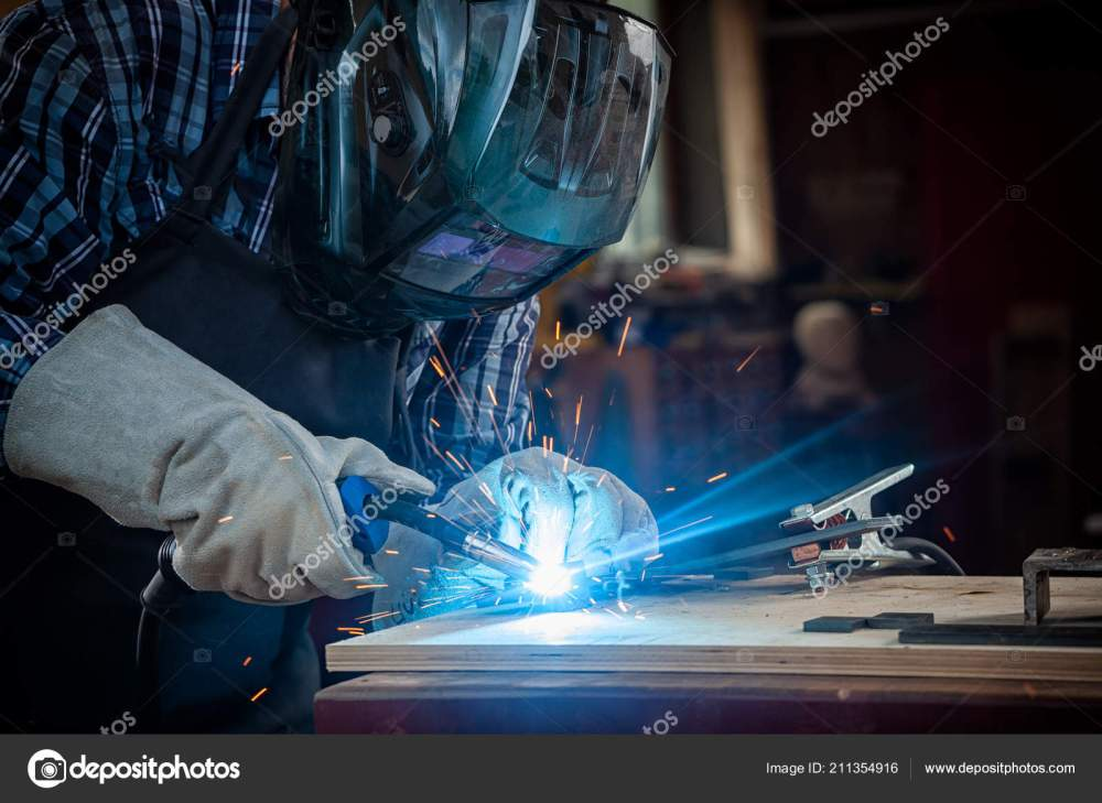 medium resolution of strong man welder work clothes hard working welds welding machine stock photo