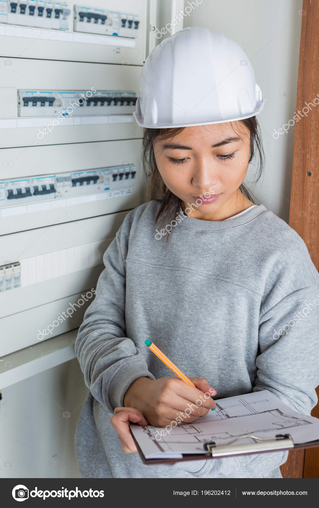 hight resolution of female electrician with clip board next to fuse box stock photo