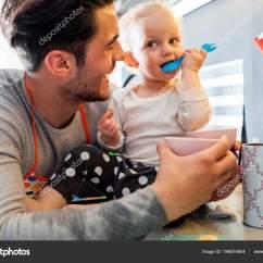 Ellas Kitchen Baby Food Table For Small 年轻的父亲与学步儿童女孩吃健康婴儿食品在厨房里 图库照片