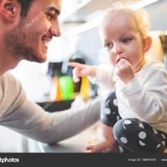 Ellas Kitchen Baby Food Magician 年轻的父亲与学步儿童女孩吃健康婴儿食品在厨房里 图库照片