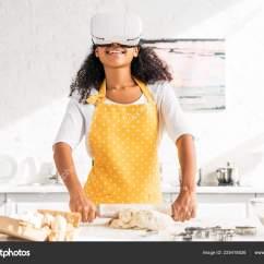 Virtual Kitchen Cafe Style Tables For 微笑的非洲裔美国女孩在围裙和虚拟现实耳机滚动面团在厨房 图库照片
